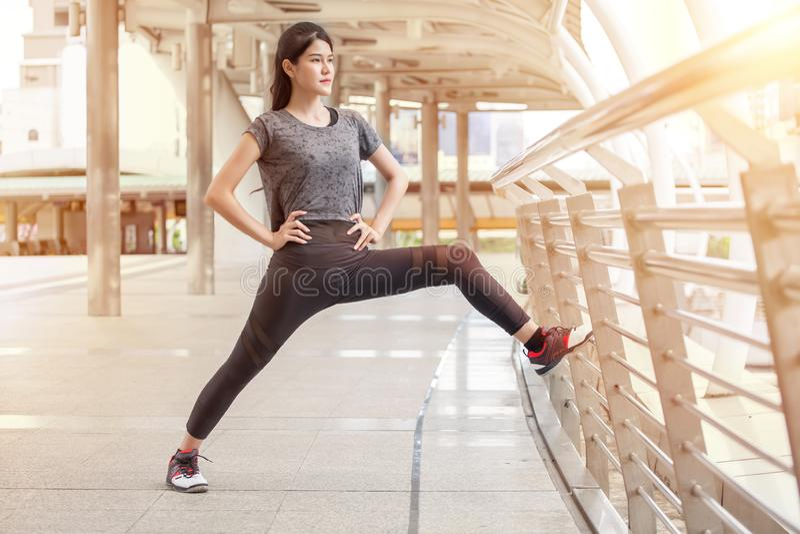 舒展在路轨桥梁锻炼的亚裔健身年轻女人腿行使在街道上在都市城市 赛跑者体育女孩准备 免版税库存照片