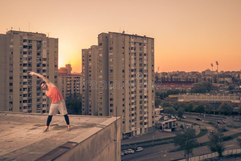 舒展大厦城市屋顶屋顶,日落日出S的运动员 库存照片