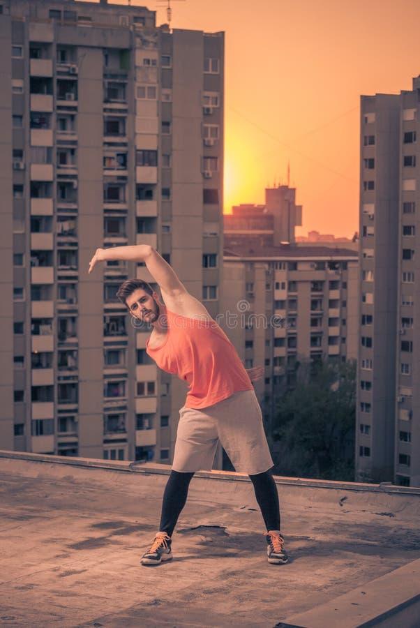 舒展大厦的运动员顶房顶屋顶,日落日出太阳, w 库存照片