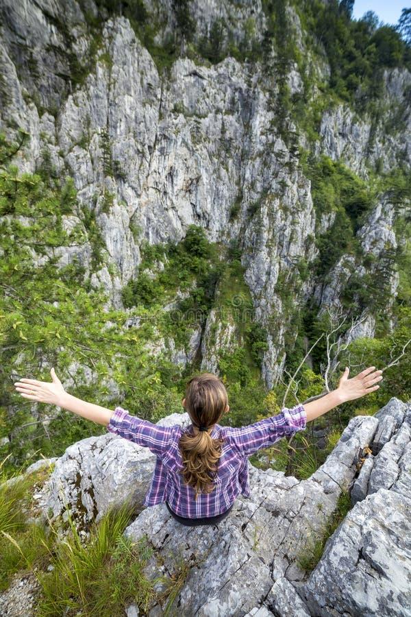 舒展她的在山的远足者少妇胳膊 免版税库存图片