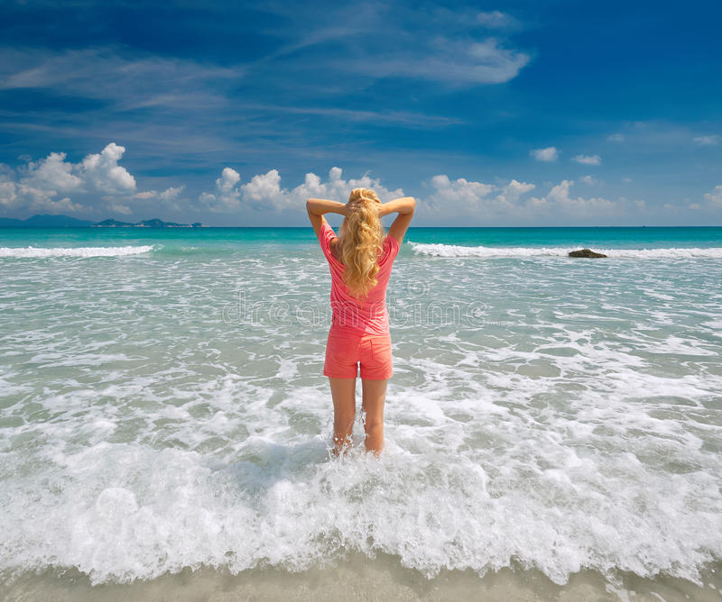 舒展她的胳膊在海滩的少妇反对天空和 免版税库存照片