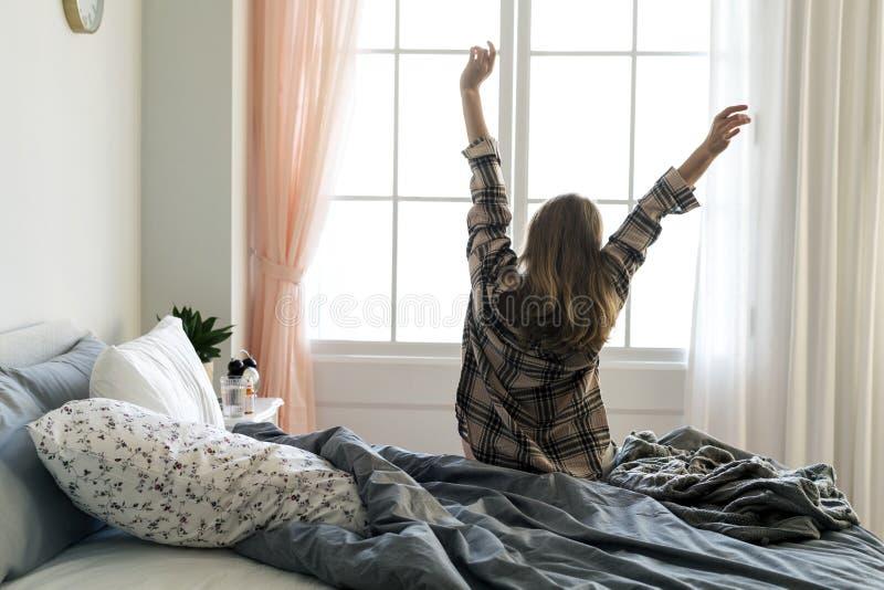 舒展她的胳膊的妇女背面图早晨 免版税图库摄影