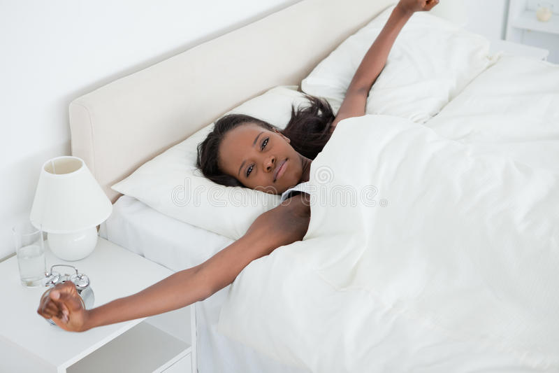 舒展她的胳膊的妇女,当醒时 库存图片