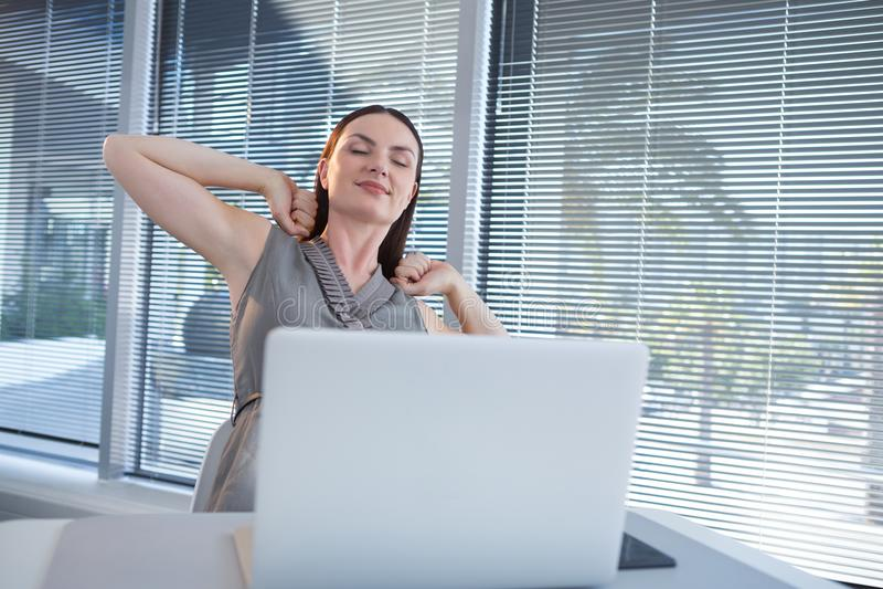 舒展她的胳膊的疲乏的女性执行委员在书桌 图库摄影