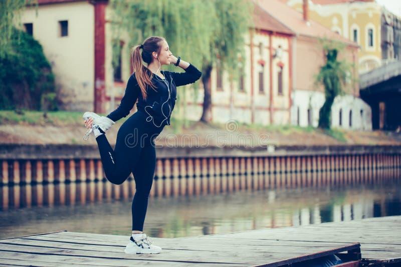 舒展她的腿的年轻女人,由河 库存照片