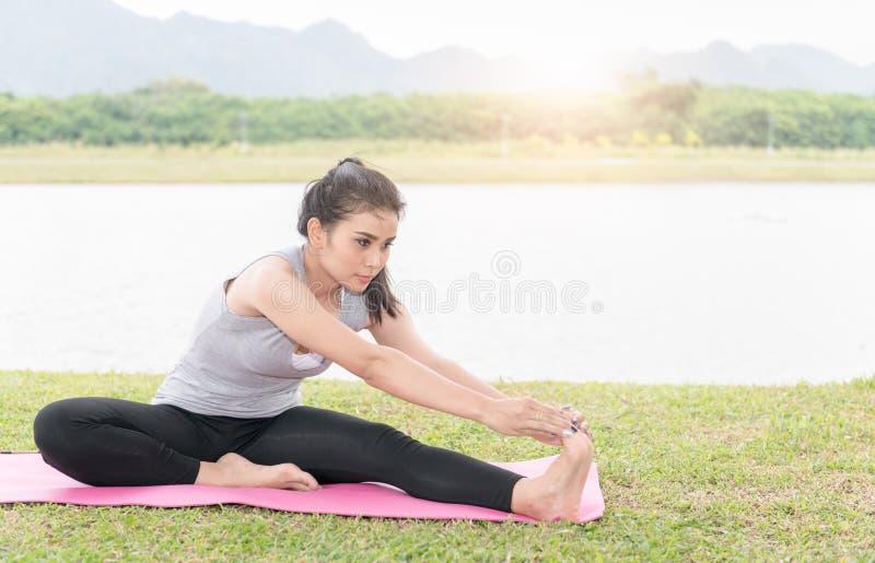 舒展她的腿的适合的亚裔妇女做准备 免版税库存照片