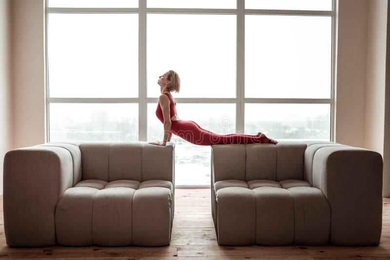舒展她的身体的灵活的短发年轻女人在瑜伽会议期间 免版税库存照片