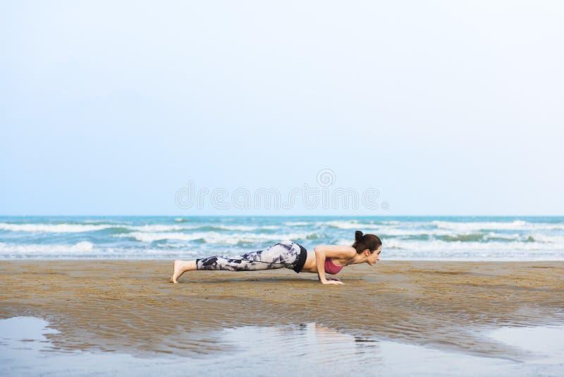 舒展导电线的妇女铺板训练健康生活方式海滩 库存照片