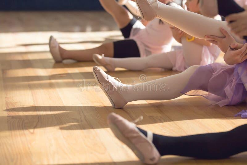 舒展小女孩的腿的创造性的芭蕾关闭,当坐在芭蕾类时的