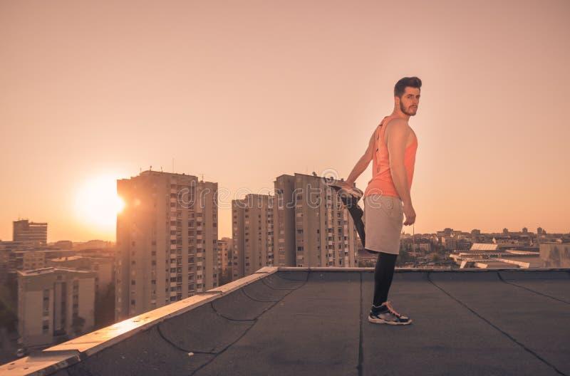 舒展屋顶屋顶,太阳日落日出的运动员人 库存照片