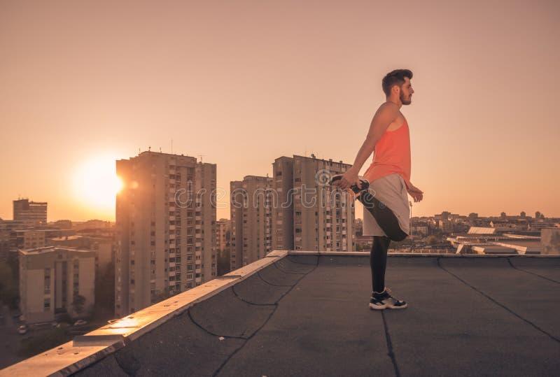 舒展屋顶屋顶,太阳日落日出的运动员人 免版税库存照片