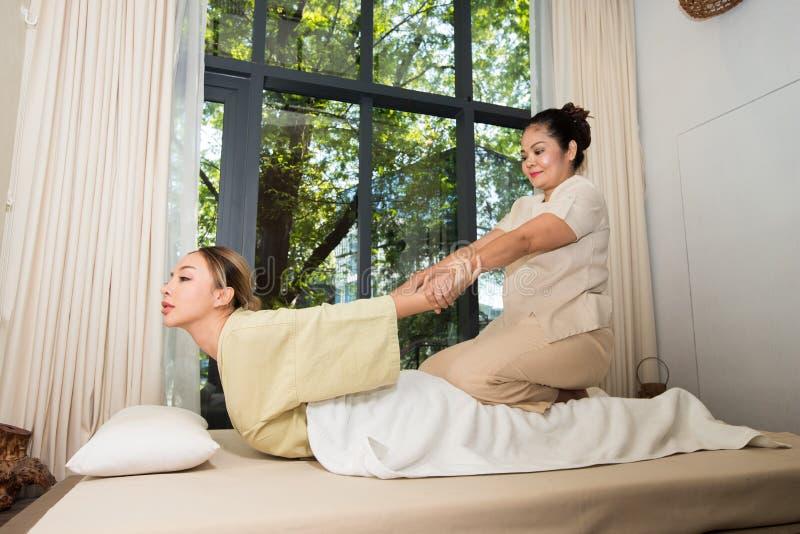 舒展弯曲的按摩肩膀的女按摩师  免版税图库摄影