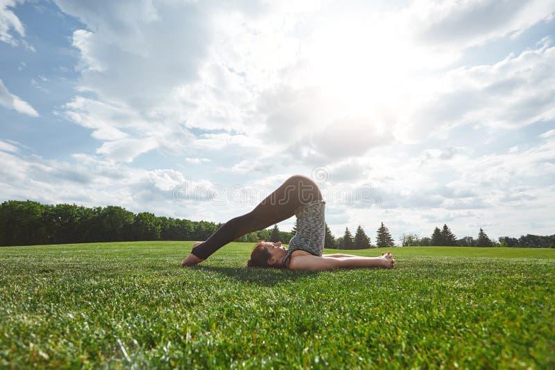 舒展执行 做瑜伽的体育衣裳的年轻女人户外在绿草 晴朗的早晨 苹果概念卫生措施磁带 库存图片