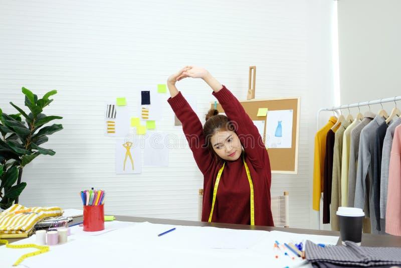 舒展放松的年轻亚裔妇女时尚编辑身体,当工作在家庭演播室,小企业主,时尚时 图库摄影