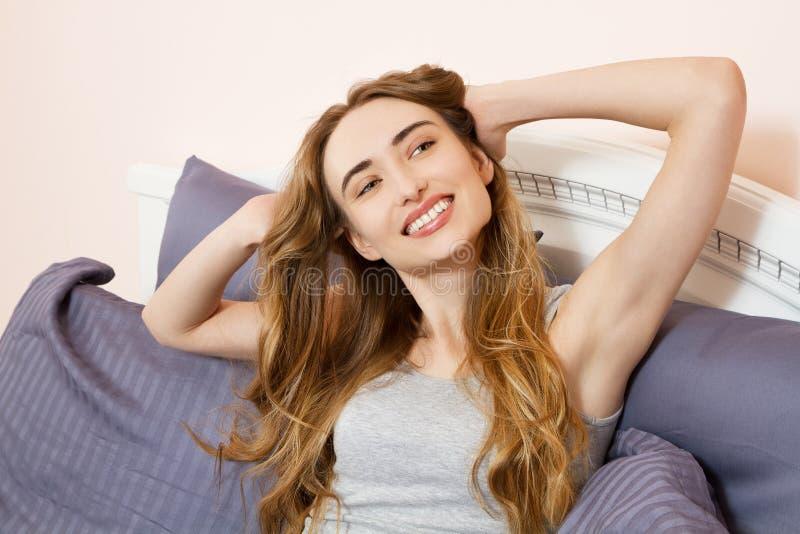 舒展早晨,在睡眠,休息日以后的逗人喜爱的女孩的愉快的美女的图片在努力星期以后 免版税图库摄影