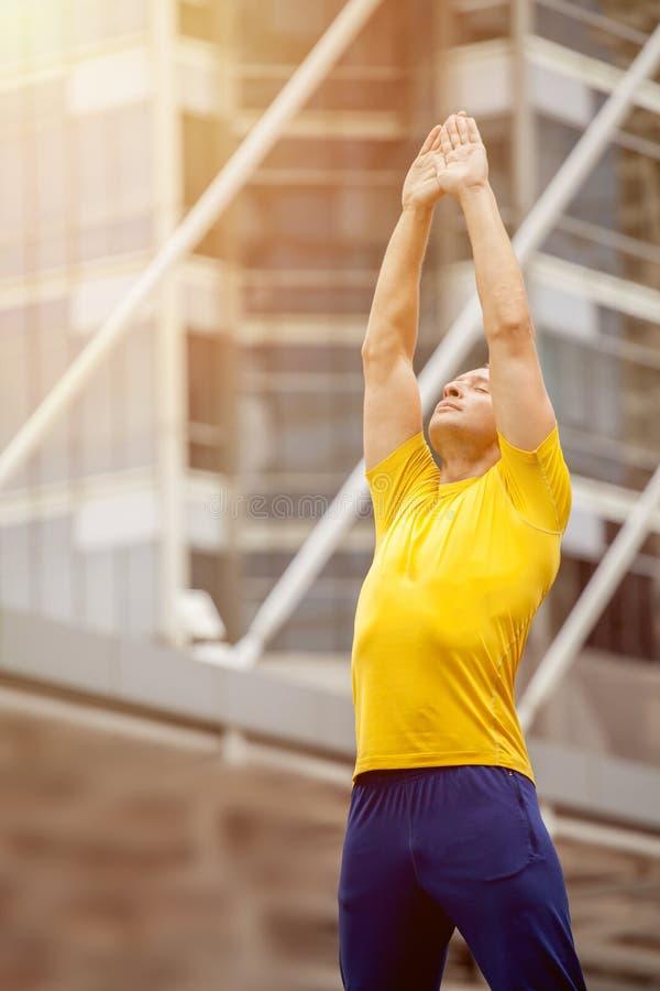 舒展的运动服的英俊的年轻体育人,当做准备在室外时的城市 早晨 免版税图库摄影