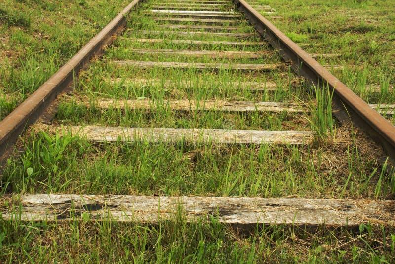 舒展老的铁路长满与绿草 免版税库存图片