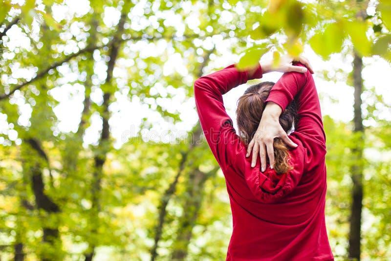 舒展胳膊和肩膀户外的年轻女人 库存图片
