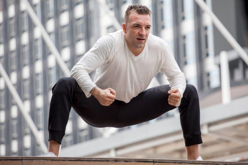 舒展腿的健身人在都市城市 体育,锻炼,锻炼,训练 库存照片