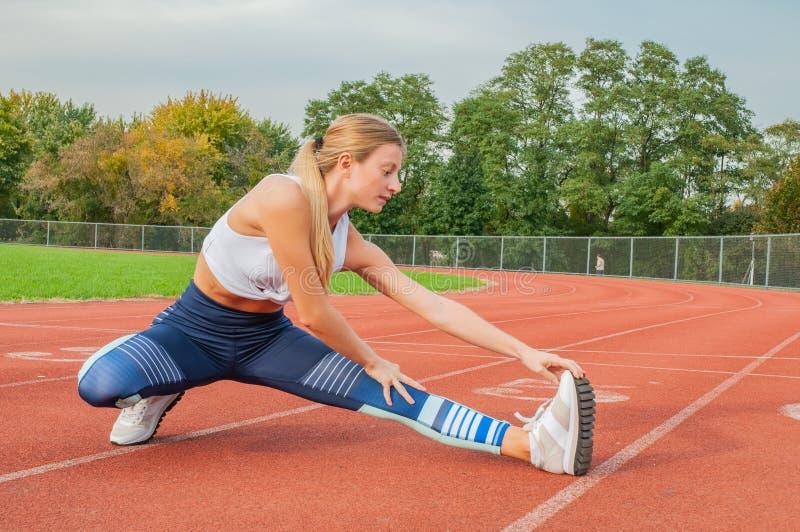 舒展腿的健身妇女在户外的奔跑前 免版税库存图片