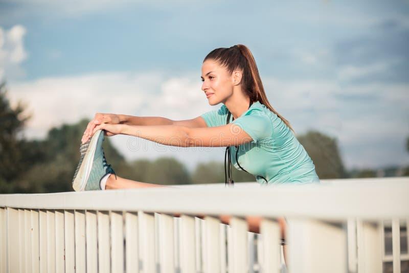 舒展腿的坚定的年轻女人在一种坚硬室外都市锻炼以后 库存图片