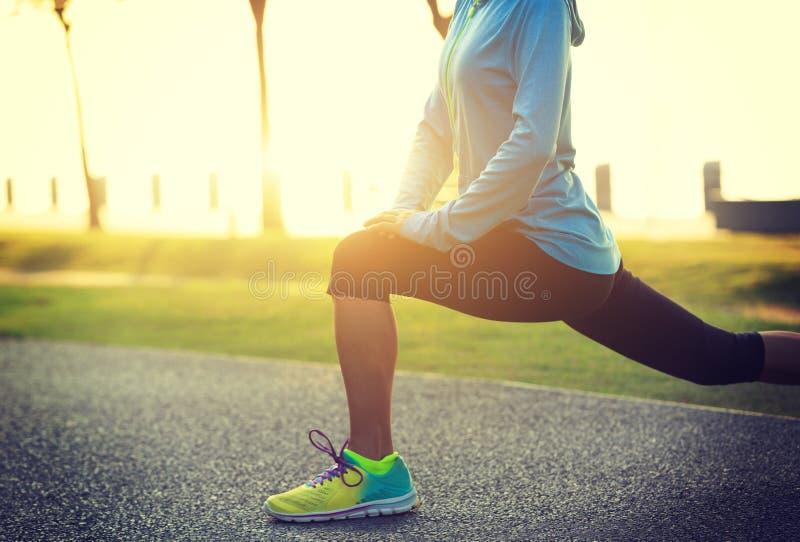 舒展腿的妇女在奔跑前在热带公园 免版税图库摄影