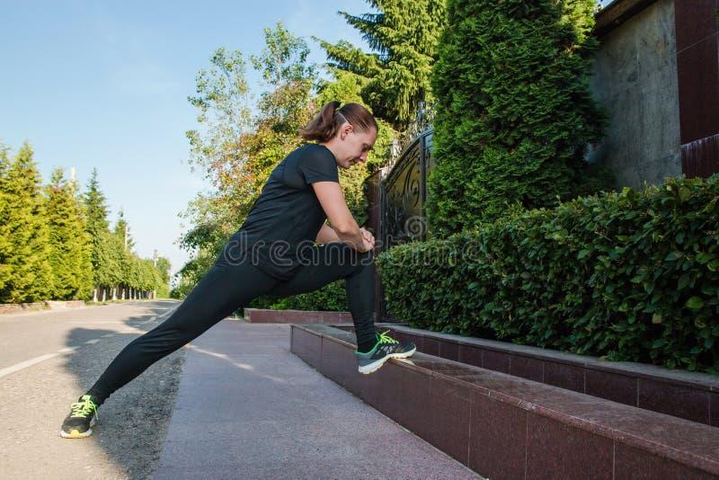 舒展腿的年轻健身妇女赛跑者在奔跑前 库存图片