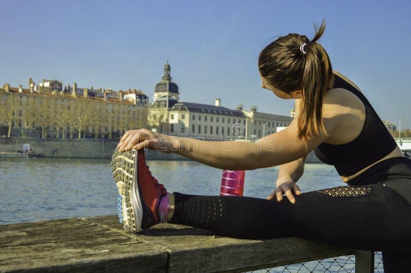 舒展腿的年轻可爱的运动的妇女在跑以后在城市 免版税库存照片