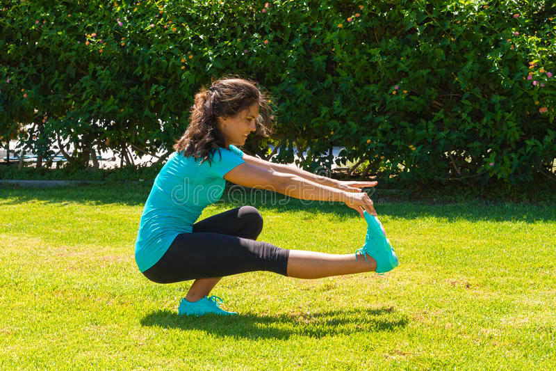 舒展腿筋的年轻运动妇女在 免版税库存图片