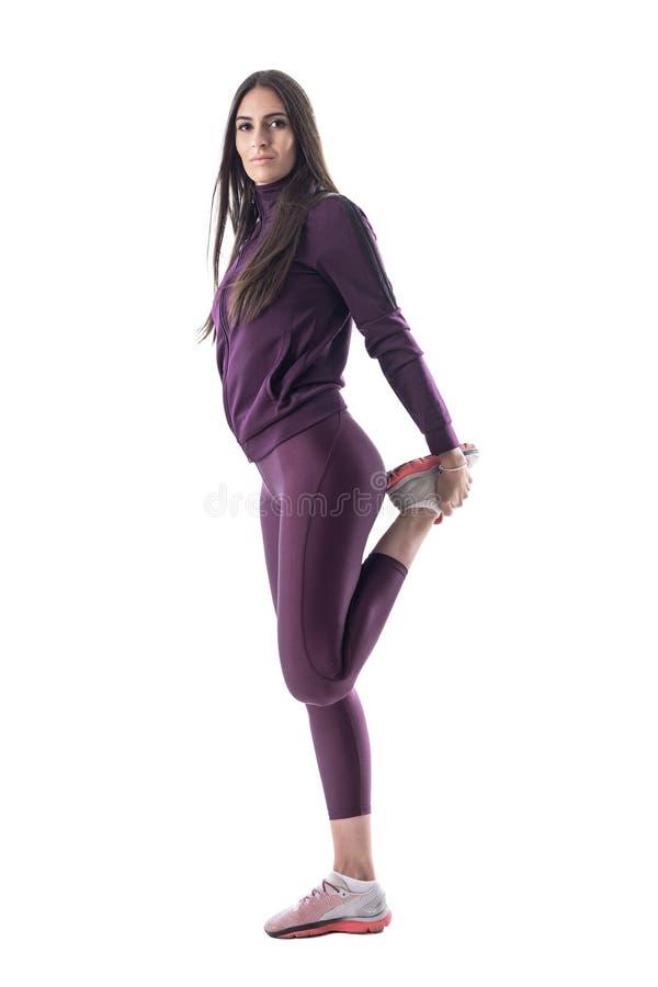 舒展腿肌肉的适合的女运动员运动员侧视图为跑做准备 免版税库存图片