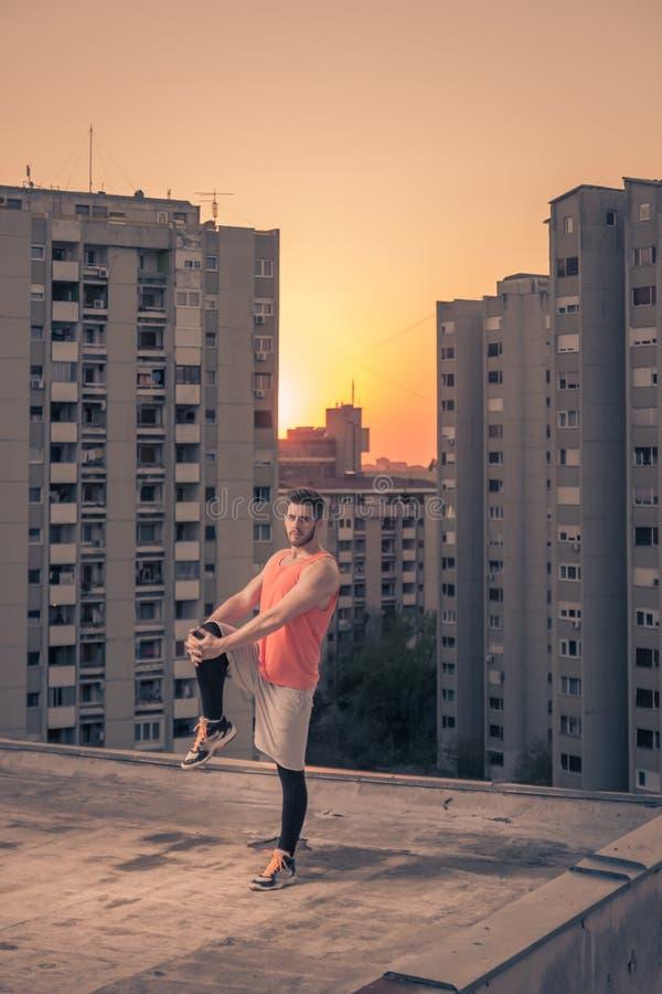 舒展腿,屋顶屋顶,日落日出太阳,修造的运动员 免版税库存图片