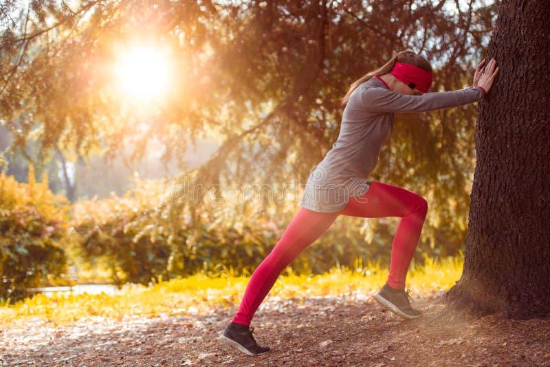 舒展锻炼训练的年轻美丽的白种人妇女 秋天连续健身女孩在城市都市公园环境里 图库摄影