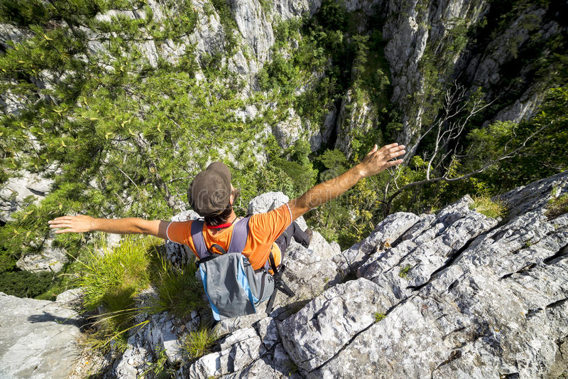 舒展他的在山的远足者年轻人胳膊 免版税库存照片