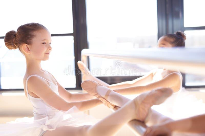 舒展他们的腿的小芭蕾舞女演员使用酒吧 免版税库存照片