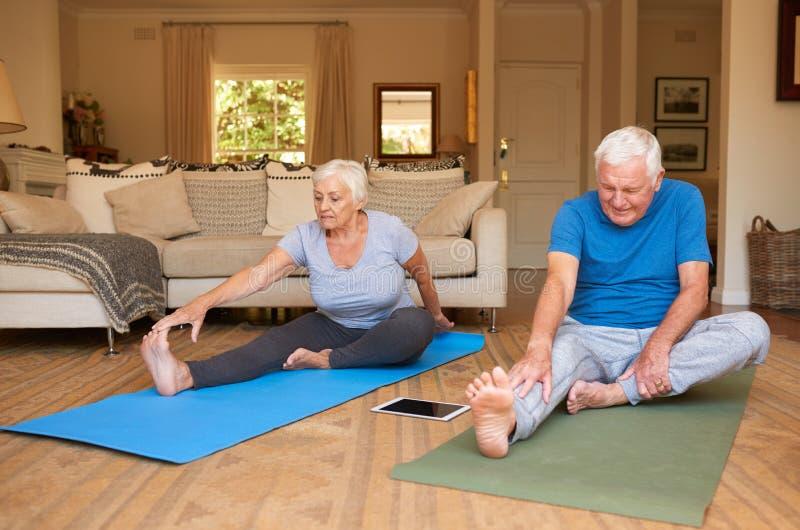 舒展活跃资深的夫妇,当一起做瑜伽在家时 免版税库存图片