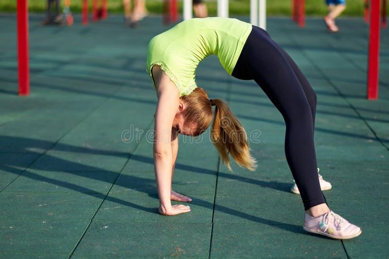 舒展danser或体操运动员妇女训练在锻炼运动场训练 做锻炼桥梁 免版税库存图片