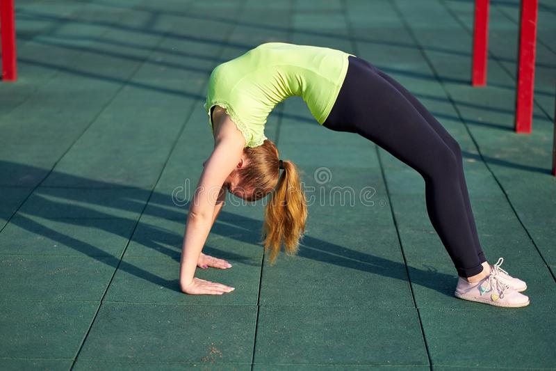 舒展danser或体操运动员妇女训练在锻炼运动场训练 做锻炼桥梁 免版税图库摄影