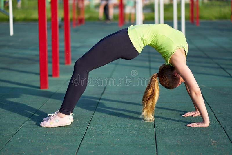舒展danser或体操运动员妇女训练在锻炼运动场训练 做锻炼桥梁 免版税库存照片