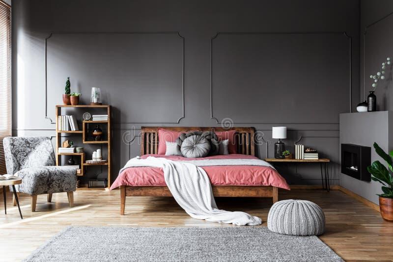舒适卧室内部的真正的照片与木床的在中间 免版税库存照片