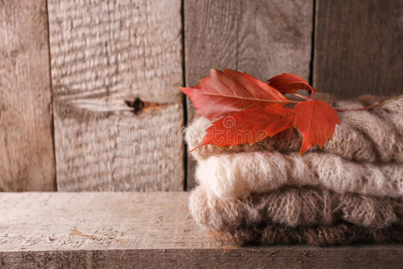 舒适和软的温暖的秋天秋天背景、被编织的毛线衣和红色叶子在一个老葡萄酒木板 周末假日在家 库存照片