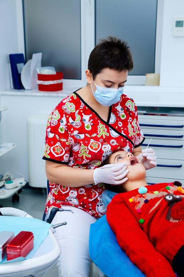 舒适安静治疗办公室儿童牙医牙小女孩青少年的红色医生新年折扣妇女干净的诊所 免版税图库摄影