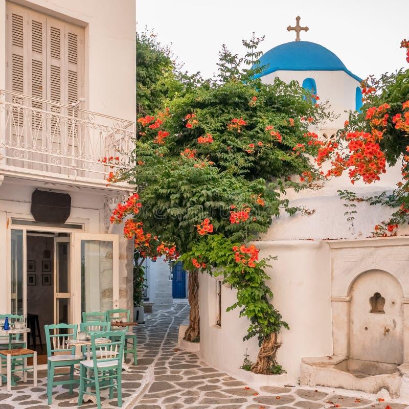舒适室外咖啡馆和传统希腊教会在美丽的狭窄的街道上在Parikia镇在帕罗斯岛海岛基克拉泽斯上 图库摄影