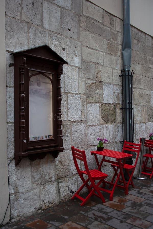 舒适室外咖啡馆红色椅子和桌在夏天雨以后 免版税库存图片
