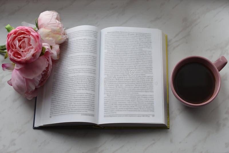 舒适家庭静物画:杯子热的咖啡、春天花和被打开的书与温暖的格子花呢披肩在窗台 春天 免版税库存照片