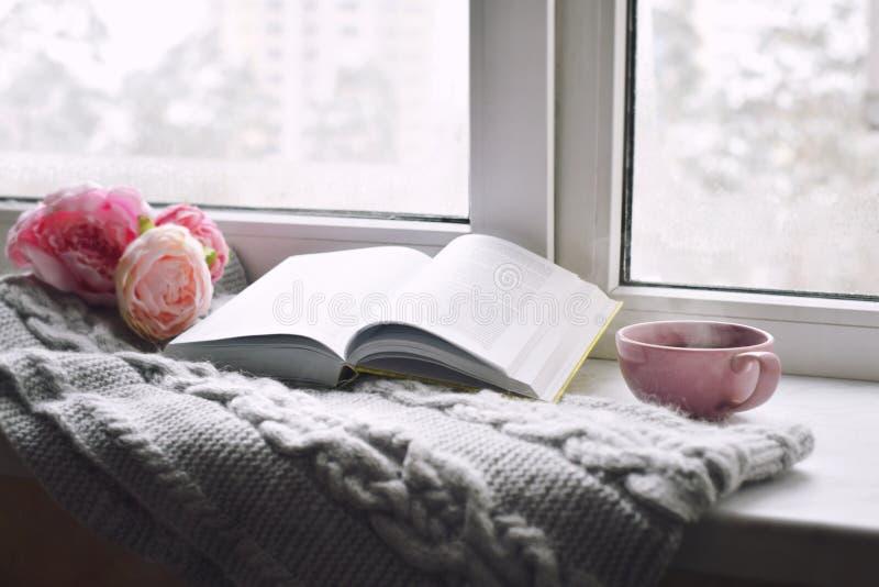 舒适家庭静物画:杯子热的咖啡、春天花和被打开的书与温暖的格子花呢披肩在窗台 春天 库存图片