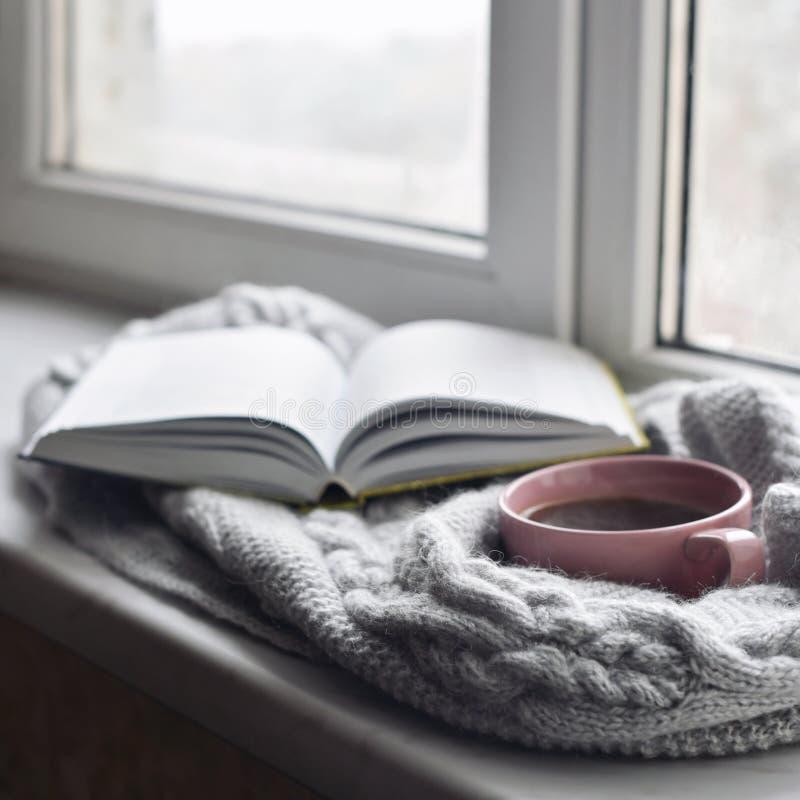 舒适家庭静物画:杯子热的咖啡和被打开的书与外面温暖的格子花呢披肩在窗台反对雪风景 图库摄影