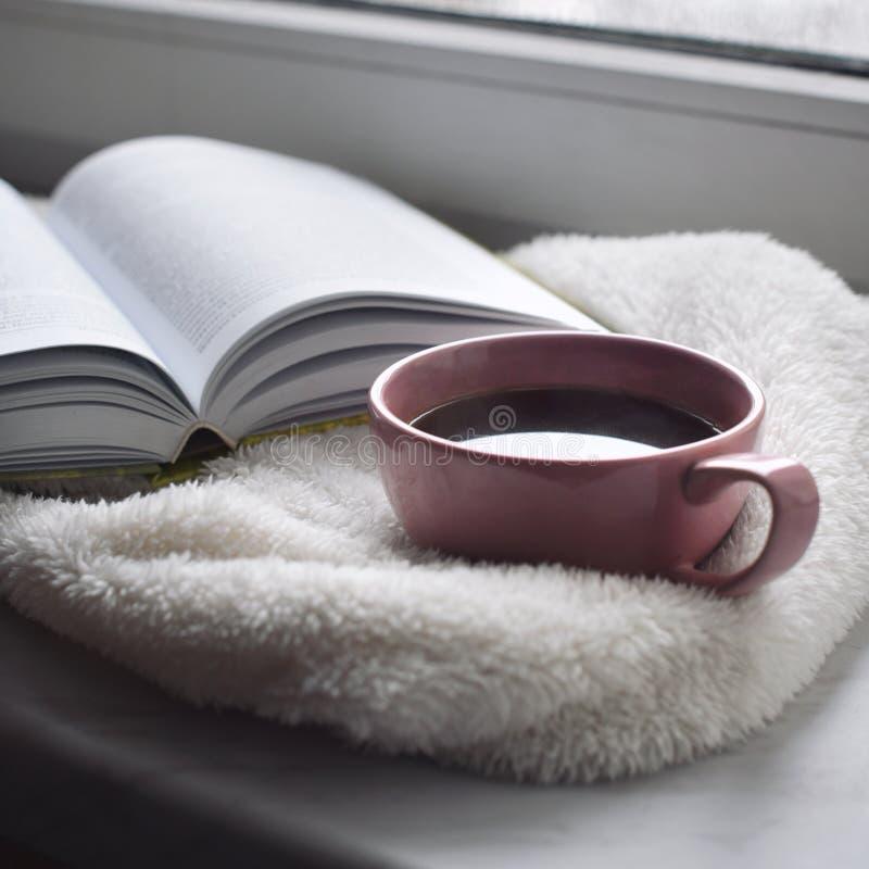 舒适家庭静物画:杯子热的咖啡和被打开的书与外面温暖的格子花呢披肩在窗台反对雪风景 免版税库存照片