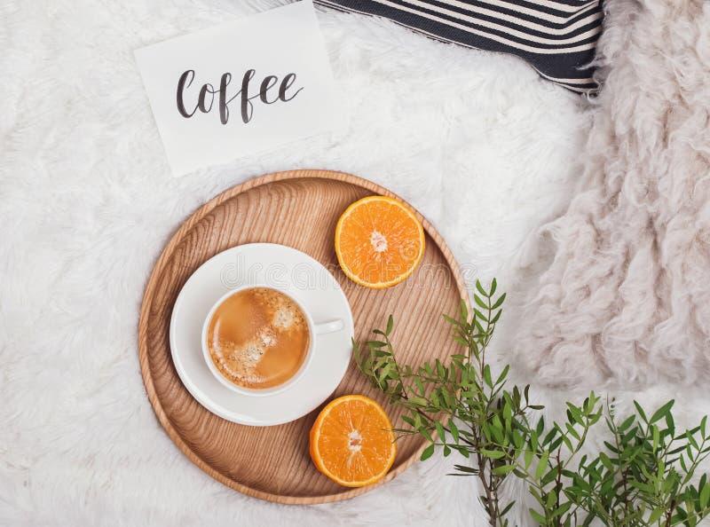 舒适平的位置用咖啡、绿色分支和桔子在床上 库存照片