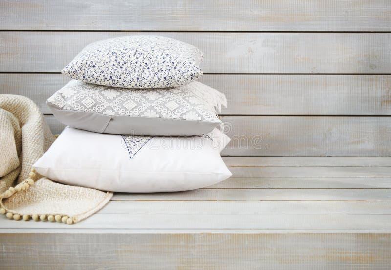 舒适枕头和格子花呢披肩在轻的木背景 库存图片