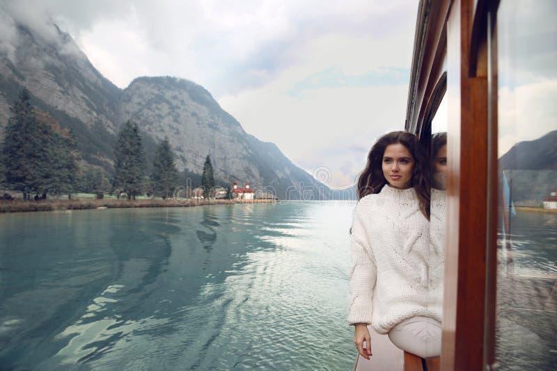 舒适毛线衣的妇女游人享用在小船的在Konigssee湖 免版税库存照片